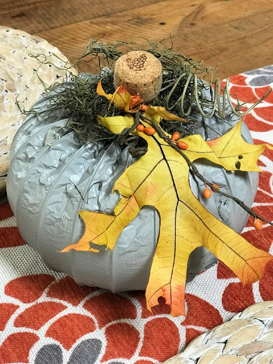 Grey Fall Pumpkin from a dryer hose with yellow leaf