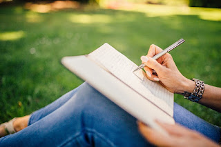 woman writing in a notebook on the grass