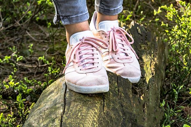 Girl Balancing Herself on a Rock wearing Pink Tennis Shoes