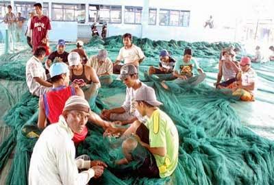 nelayan perbaiki jaring ikan