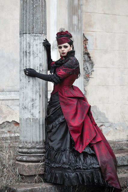 Woman wearing elegant gothic victorian red and black dress with gloves, hat, birdcage veil, and jewelry