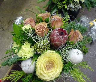 Bukett med Skimmia, Protea, Brassica, roser og nellik