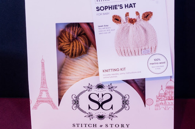 A gift package with yarn and needles visible through a window and a label with a giraffe hat based on Sophie La Girafe