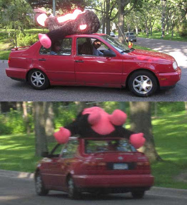 Red Jetta car with a brown and hot pink giant monkey tied to the roof