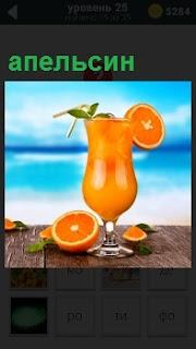 На фоне голубого моря на столе стоит апельсиновый сок в стакане и сам апельсин порезанный дольками