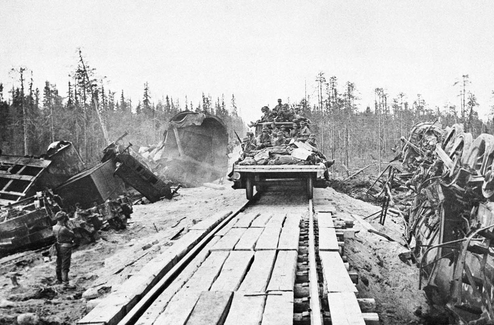 A Finnish troop train passes through a scene of an earlier explosion which wrecked one train, tearing up the rails and embankment, on October 19, 1941.