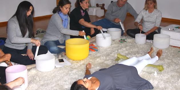 Grupo de personas tocando cuencos de cuarzo en casa Guangualí