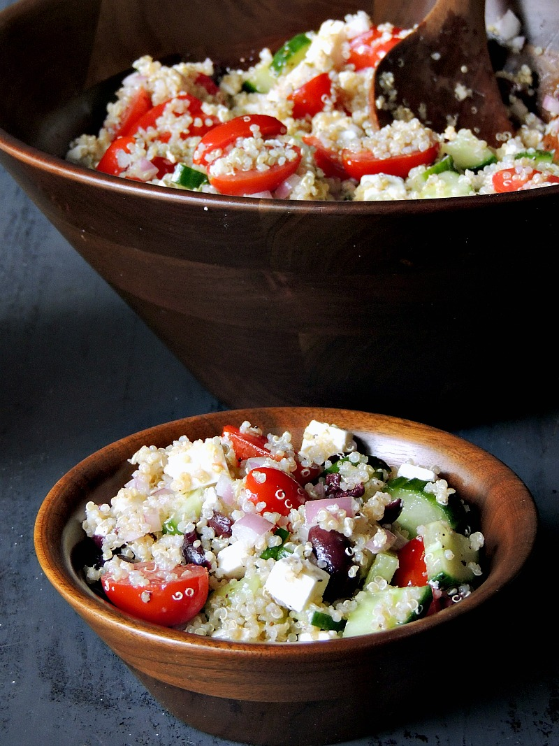 Mediterranean Quinoa Salad in a wooden salad bowl on a blue table.