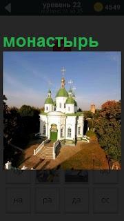 Белокаменный с зелеными куполами монастырь освещен солнечными лучами утром