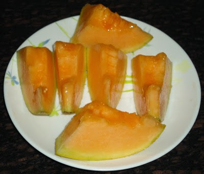 cut he muskmelon into long lieces - making kharbuja juice recipe