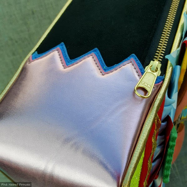 side of handbag in metallic and black with jagged edge trim