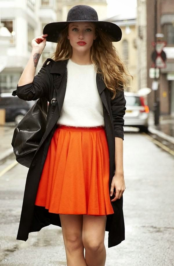 saia rodada laranja abobora com blusa branca sobretudo e chapéu preto