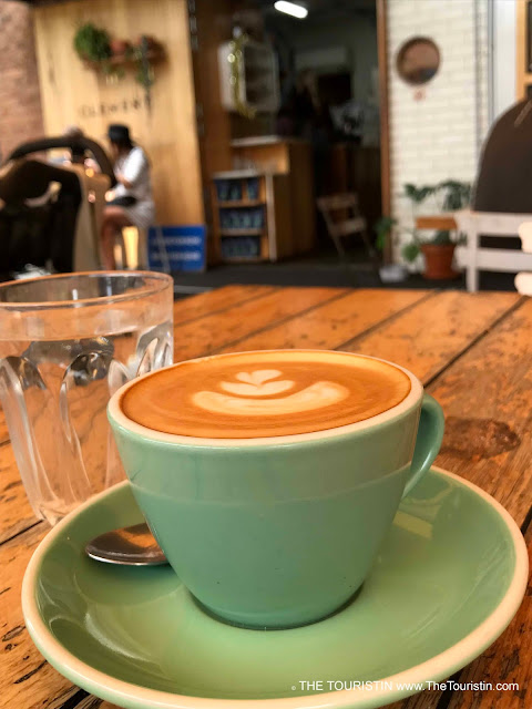 A Flat White espresso drink in a light green cup and a glas of water on a rustic wooden table