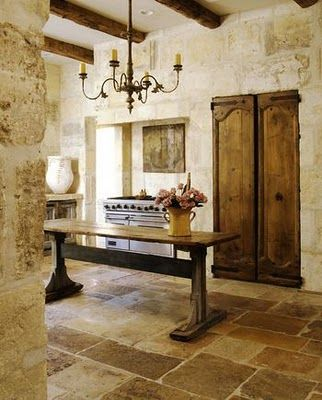 French farmhouse kitchen with stone floor and walls, chandelier, and rustic farm table