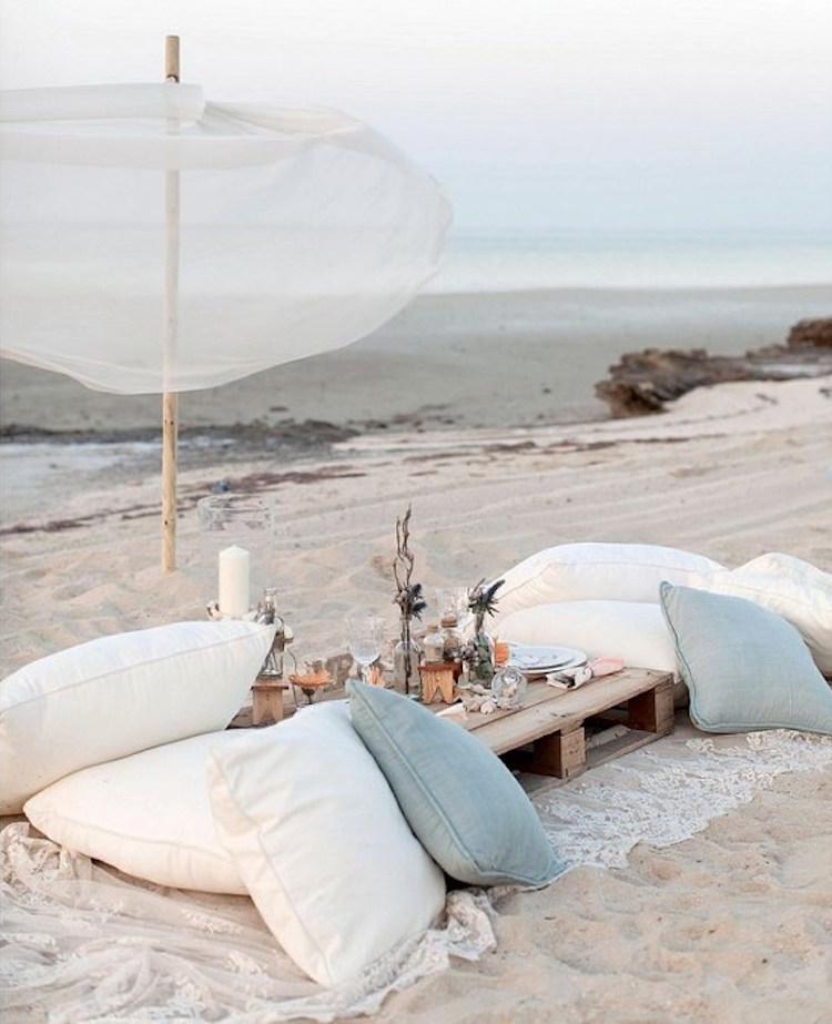 cena en la playa, almohadas, palets