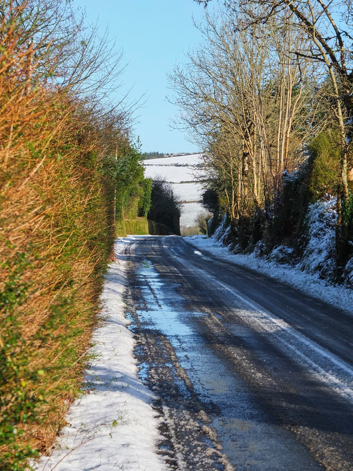 Snow melting on a county road in the mountains in North Cork.