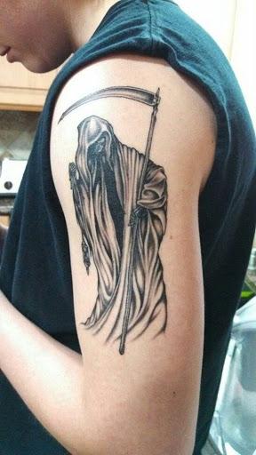 Um preto com tinta Grim Reaper tatuagem com a foice. Este é o clássico Grim Reaper concepção que as pessoas têm sido familiar. A ligeira face do reaper é mostrado e ele lhe dá um vislumbre do esqueleto da face.