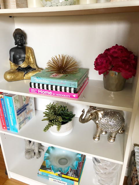 an organized and styled bookshelf with books and decor items