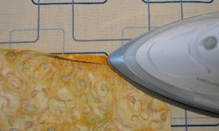 On the ironing board, the top hem has been folded once and the iron on the right hand side is pressing down the fold.