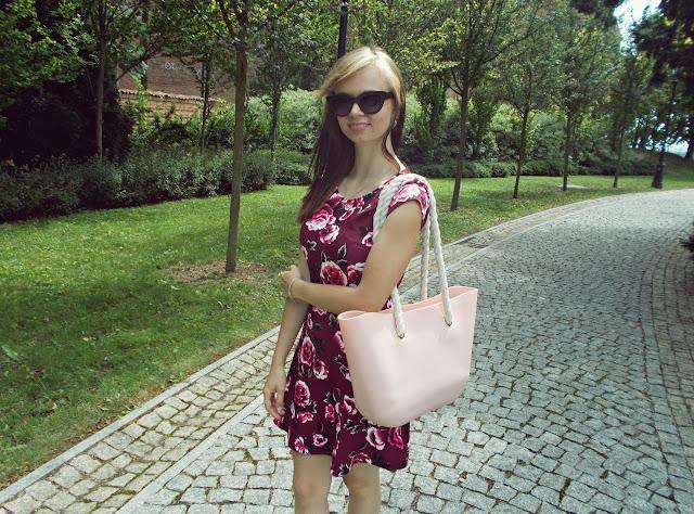 Sukienka w kwiaty i różowa torebka
