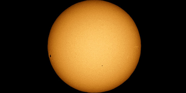 The transit of Mercury of November 2006. Mercury appears as a small circle in the lower half of the image, and has quite a different appearance to the sunspot groups on the right and left hand limbs of the Sun. Credit: TheBrockenInAGlory.