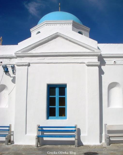 niebieskła ławeczka pod niebieskim oknem białej ściany greckiej cerkwii Mykons Cyklady
