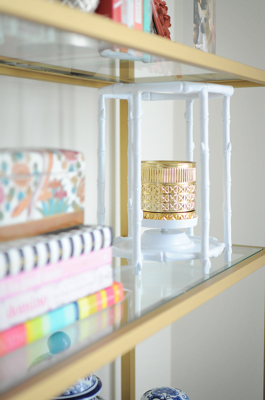 Metallic candle in a white bamboo hurricane candle holder adds a metallic touch to a black and gold bookshelf or bookcase.