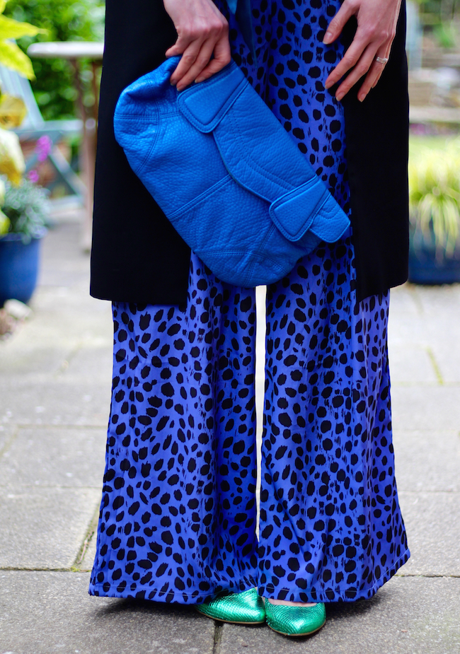 Fake Fabulous | Electric blue jumpsuit, blue clutch, green shoes, black coat and a chunky necklace.