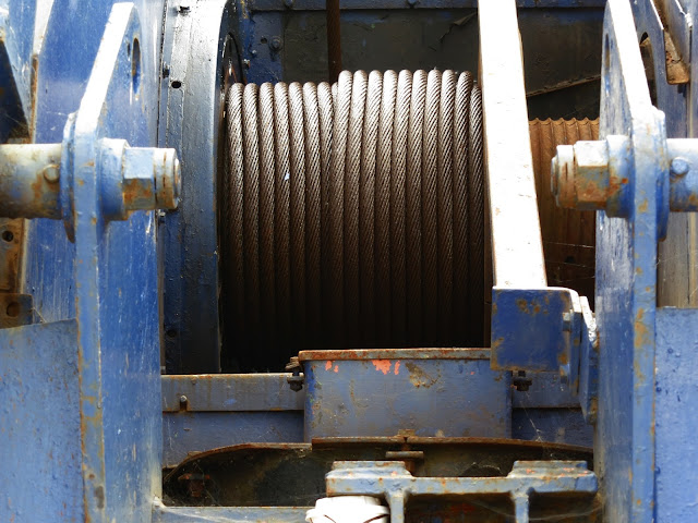 Coil of metal rope wound into blue machine. (At foot of crane?)