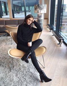 Девушка в черных джинсах и черном свитере в красивом доме