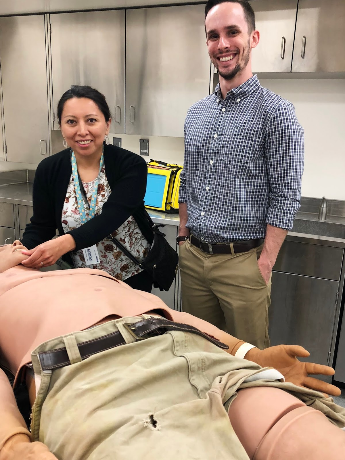 a man and women pose or a photo with a medical mannequin