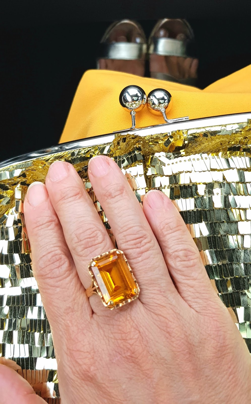 Close up of a baguette shaped citrine ring against a gold sequin bag.