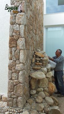 Bizzarri, da Bizzarri Pedras, fazendo os últimos reparos em lago de carpas com pedras do rio com a cascata com pedra do rio junto a parede revestida de pedra moledo em casa em condomínio em Atibaia-SP. 18 de maio de 2017.