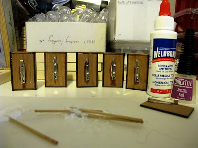 Row of brooches, showing the backs with pins just glued on, next to two bottles of glue.