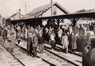 A photograph showing a crowd of figures at a train station.