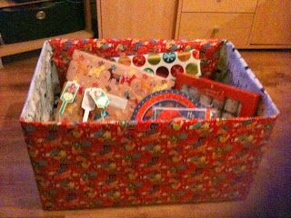 Cardboard box wrapped in Christmas paper packed with items for the Christmas Eve hamper