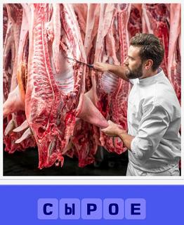 мужчина режет ножом сырое свежее мясо, висящее на крюках