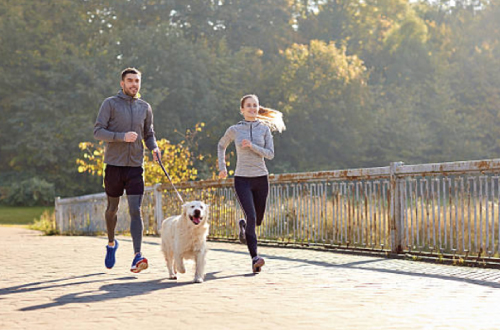 man and woman running with dog