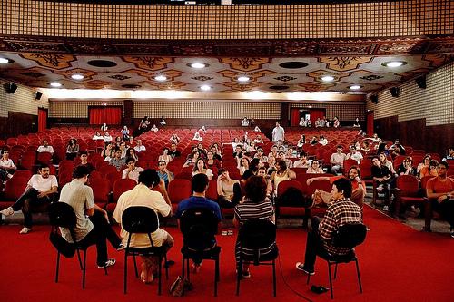 Photographie de personnes, débattant, dans une salle.