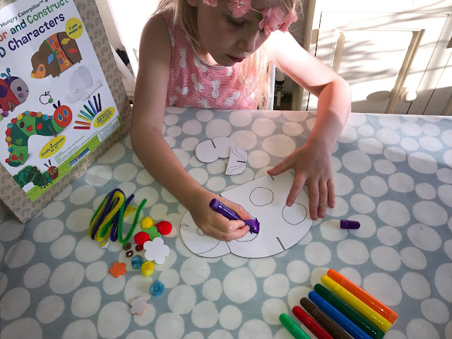A young girl colouring in a cardboard ladybird