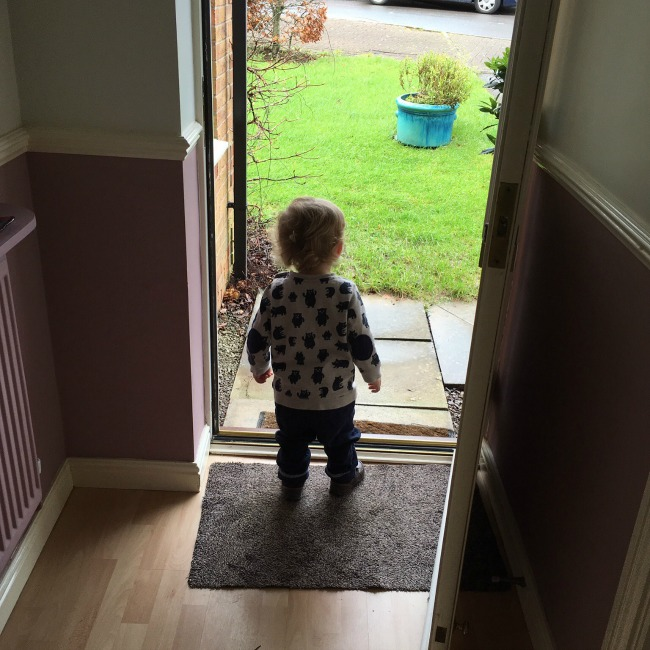 Toddler stood by open front door looking out