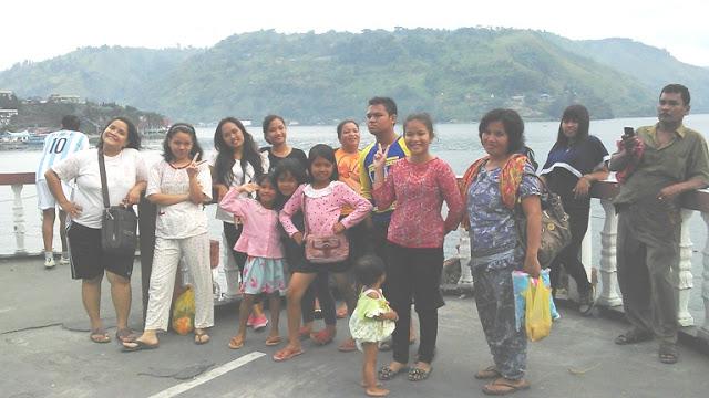 Wisatawan Dalam Negeri sedang Foto Bersama dan Menikmati Keindahan Alam Wisata di Danau Toba