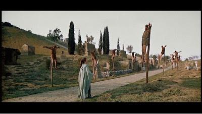 """Εξεγερμένοι σκλάβοι από τον στρατό τού Σπάρτακου σταυρωμένοι στην Απία Οδό το 71 """"π.Χ."""". Στιγμιότυπο από την ταινία Σπάρτακος του Στάνλεϋ Κιούμπρικ (1960)."""