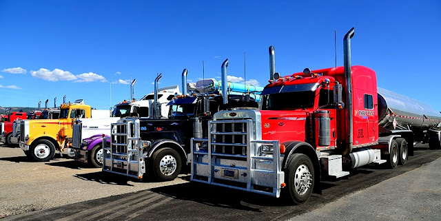 Image Attribute: The file photo of American semi-trailers in a parking lot/ Source: Pixabay.com