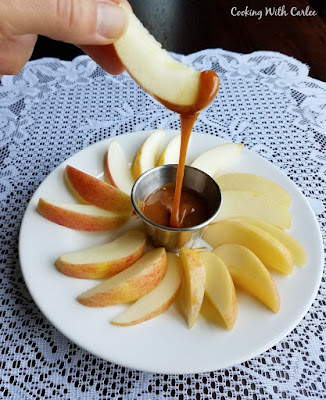 dipping apple slices into a container of homemade cajeta