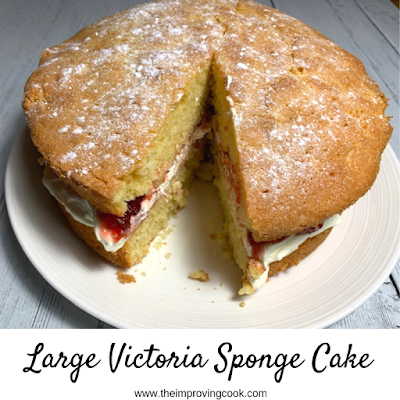 Large Victoria Sponge cake on a white plate, with one slice cut out.