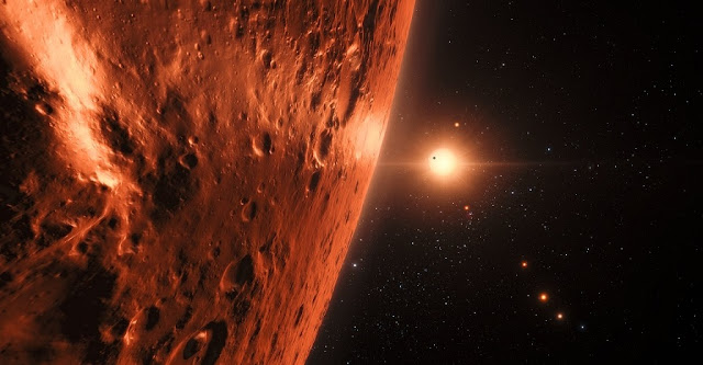 This artist's impression shows the view from the surface of one of the planets in the TRAPPIST-1 system. At least seven planets orbit this ultracool dwarf star 40 light-years from Earth and they are all roughly the same size as the Earth. Several of the planets are at the right distances from their star for liquid water to exist on the surfaces.  This artist's impression is based on the known physical parameters of the planets and stars seen, and uses a vast database of objects in the Universe.  Credit: ESO/N. Bartmann/spaceengine.org