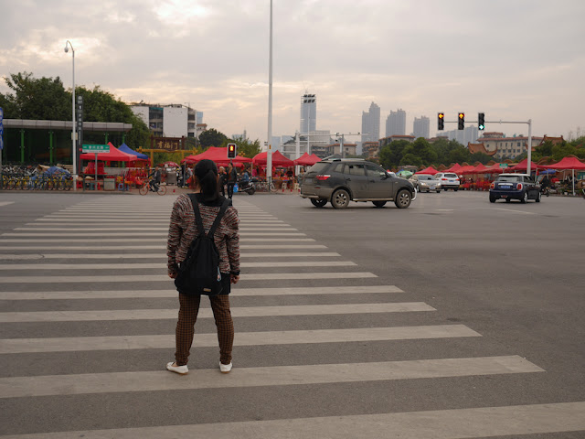 woman waiting to cross Huangxing North Road at the intersection with Kaifusi Road