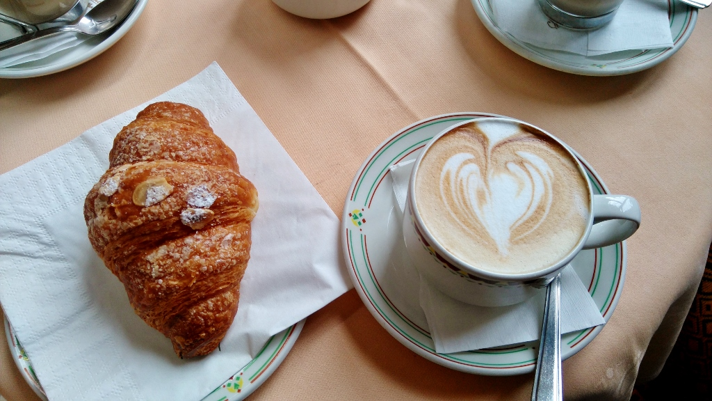 Almond pastry and cappucino for breakfast in Milan