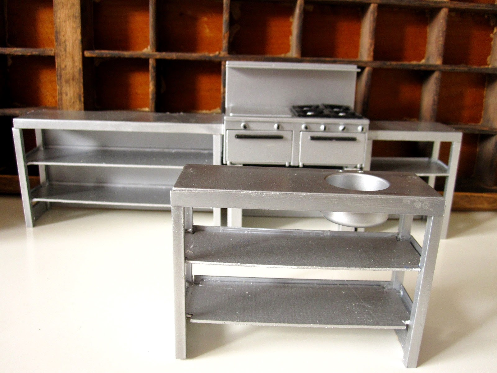 Modern dolls' house miniature steel kitchen units and shelves.